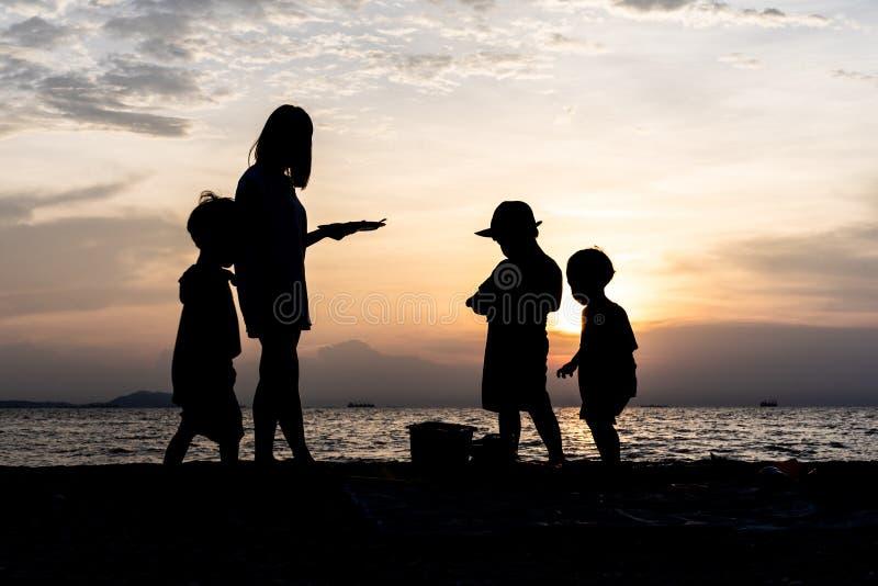 A silhueta das crianças e da mãe na praia na noite fotografia de stock