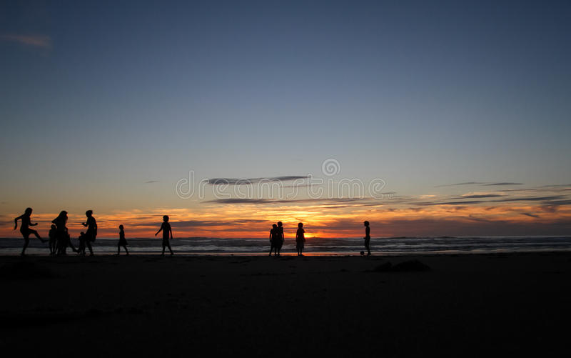 Silhueta das crianças que jogam na praia imagens de stock