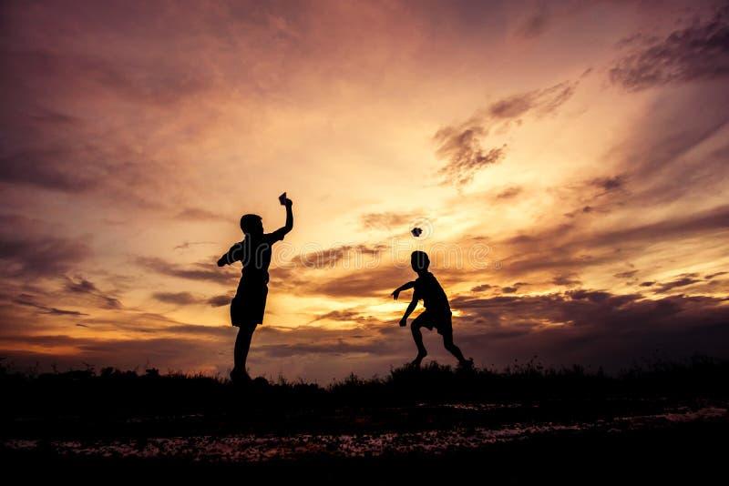 Silhueta das crianças que jogam o avião de papel no por do sol imagem de stock royalty free