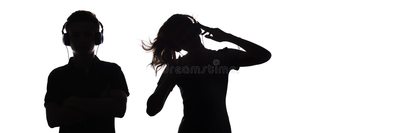 A silhueta das figuras adolescentes nos fones de ouvido que escutam a música, o indivíduo e a menina estão dançando com mãos acim fotos de stock