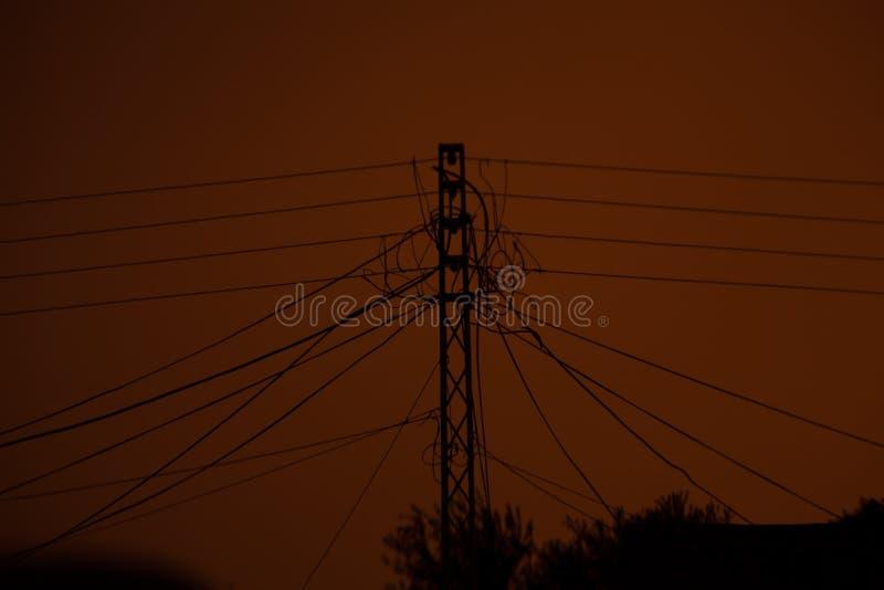 Silhueta das linhas elétricas e do polo da eletricidade fotografia de stock