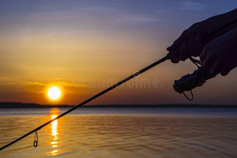 Silhueta das mãos do pescador com pesca da haste de gerencio no fundo do por do sol fotografia de stock