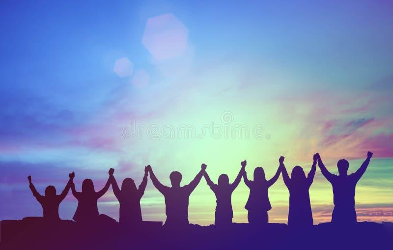 Silhueta das mãos felizes da posse dos trabalhos de equipe acima como um negócio bem sucedido, vitória Realização do objetivo de  imagem de stock