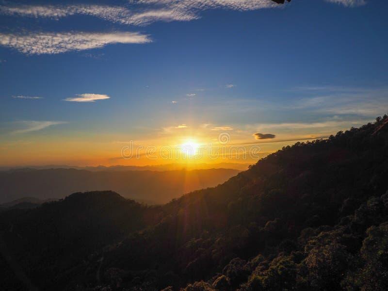 A silhueta das montanhas e árvores enquanto o sol se põe no topo Pui ko, Sop Moei, Mae Hong Son, Tailândia imagens de stock