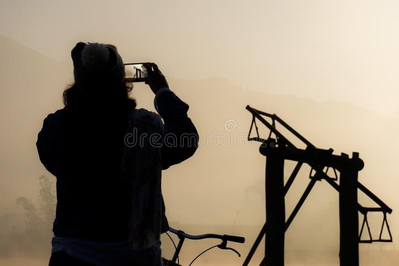 A silhueta das mulheres toma a uma foto a roda de ferris de madeira fotos de stock