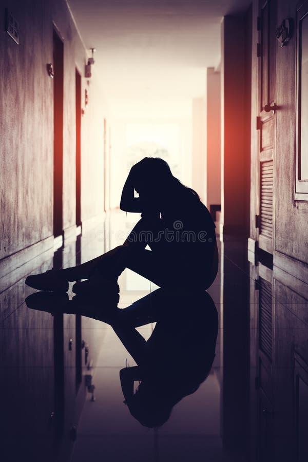 Silhueta das mulheres tristes e deprimidas que sentam-se na passagem do condomínio ou do escritório foto de stock