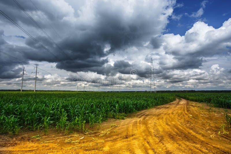 Silhueta das torres elétricas de alta tensão do pilão no fundo de nuvens de tempestade bonitas perto da estrada amarela da areia fotos de stock royalty free