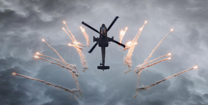 Silhueta de alargamentos de um acendimento do helicóptero de ataque fotos de stock