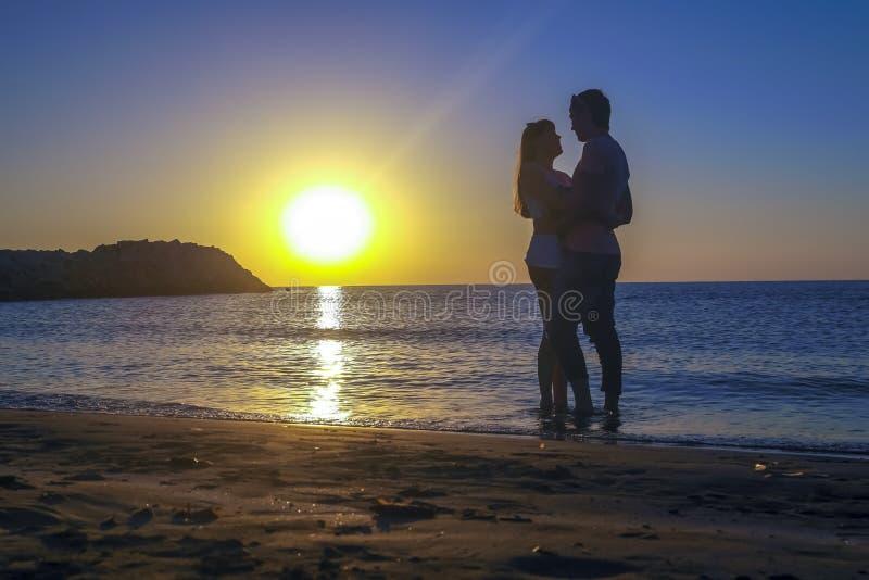 Silhueta de amantes românticos que encontram o pôr do sol na costa marítima Silhueta de amantes românticos que encontram o pô foto de stock