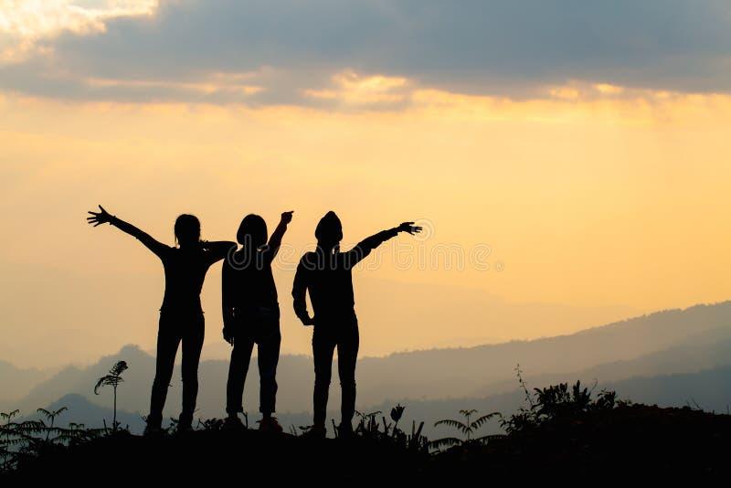 Silhueta de amigos felizes no c?u do por do sol que nivela o fundo do tempo, grupo de jovens que t?m o divertimento em f?rias de  foto de stock