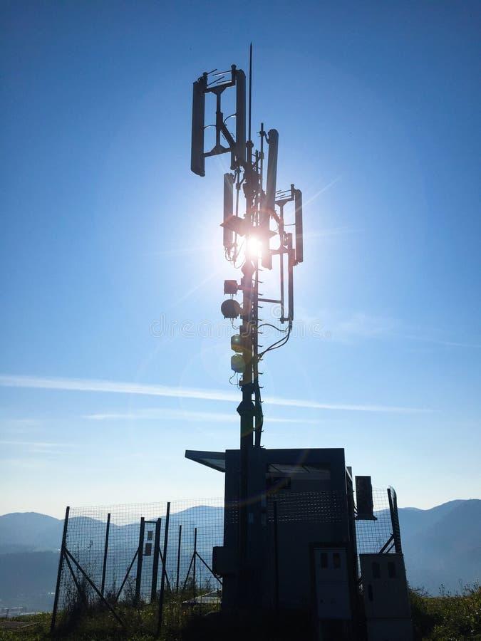 Silhueta de antenas celulares altas de uma esta??o base da telecomunica??o em um dia ensolarado imagens de stock royalty free
