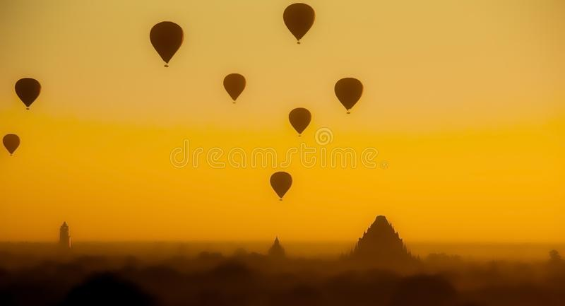 Silhueta de balões de ar quente sobre os templos de Bagan Fundo alaranjado do céu do por do sol foto de stock royalty free