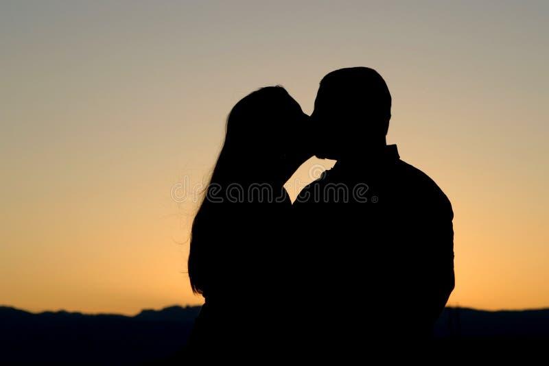 Silhueta de beijo dos pares fotografia de stock