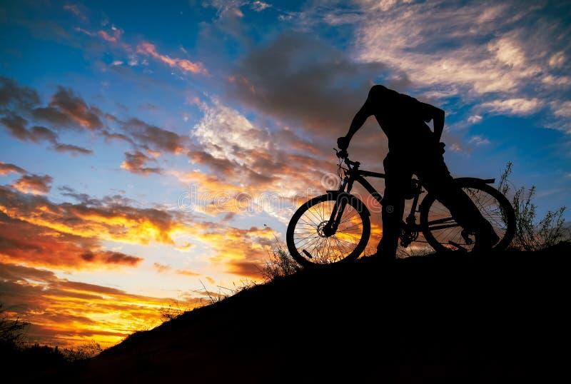 Silhueta de desportistas a andar de bicicleta no prado no lindo pôr do sol imagens de stock