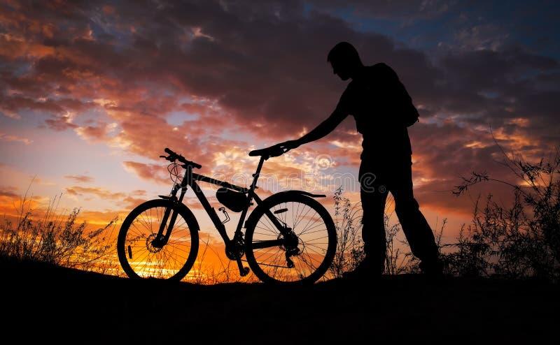 Silhueta de desportistas a andar de bicicleta no prado no lindo pôr do sol. Jovem com câmera e bicicleta imagem de stock