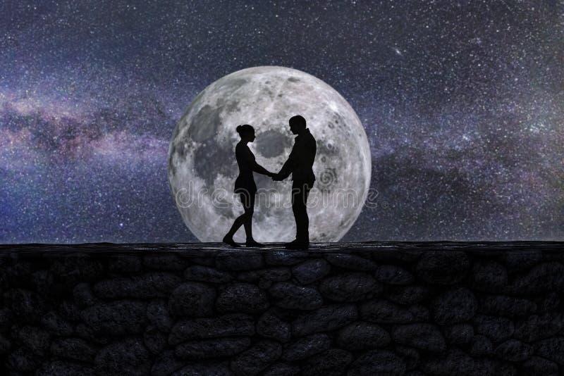 Silhueta de dois amantes antes de uma lua gigante imagem de stock royalty free