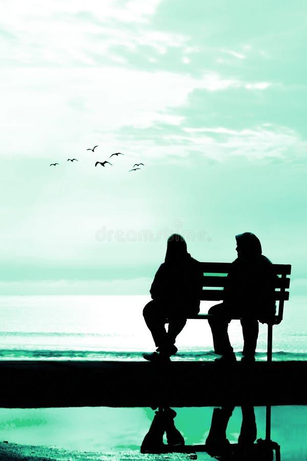 Silhueta de dois amigos que sentam-se no banco de madeira perto da praia imagem de stock royalty free