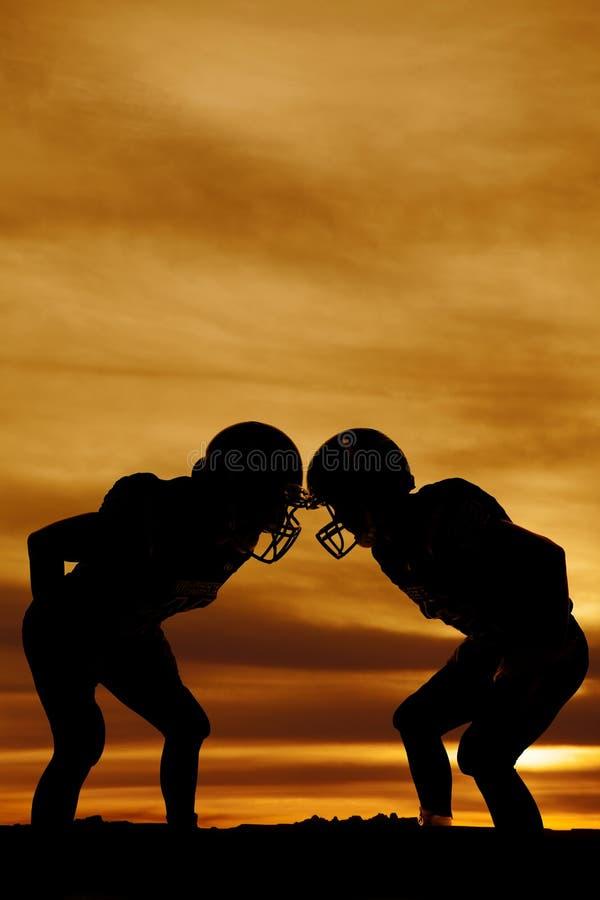 Silhueta de dois jogadores de futebol no suporte do por do sol fotos de stock