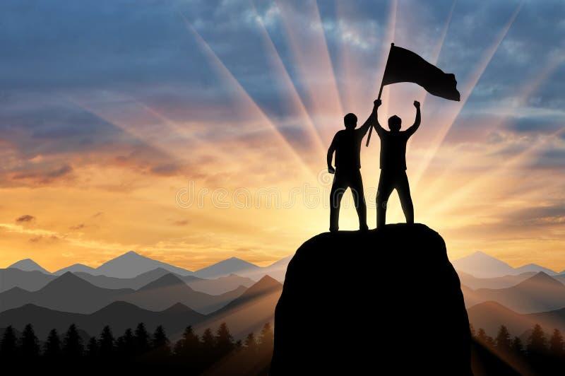 Silhueta de dois montanhistas em uma parte superior da montanha com uma bandeira em sua mão foto de stock royalty free