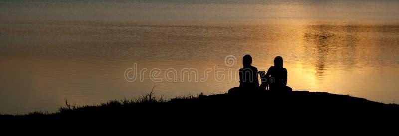 Silhueta de duas meninas e de um cachorrinho que senta-se na praia contra um fundo do espaço de água alaranjado brilhante ilumina foto de stock