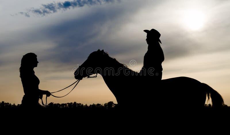 Silhueta de duas mo?as com um chap?u e um cavalo no fundo do c?u do por do sol foto de stock
