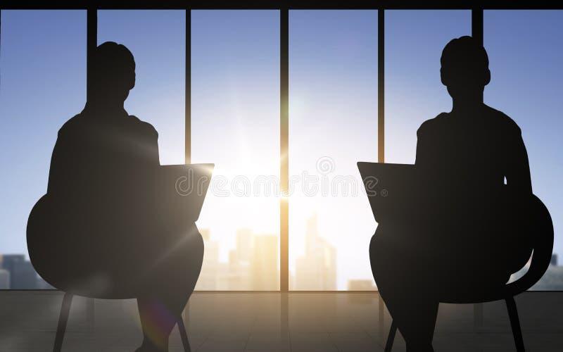 Silhueta de duas mulheres de negócio com portátil ilustração royalty free