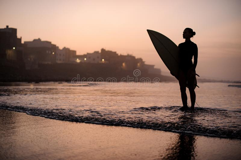 Silhueta de garota no traje de mergulho na praia segurando uma prancha amarela de surfe nas mãos foto de stock
