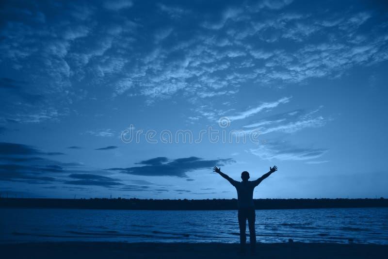 Silhueta de homem com braços estendidos contra céu nublado à noite perto do lago Banner natural com cor do ano 2020 - imagem de stock royalty free