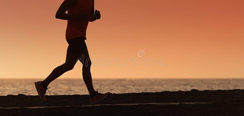 Silhueta de homem running no céu impetuoso do por do sol imagens de stock royalty free