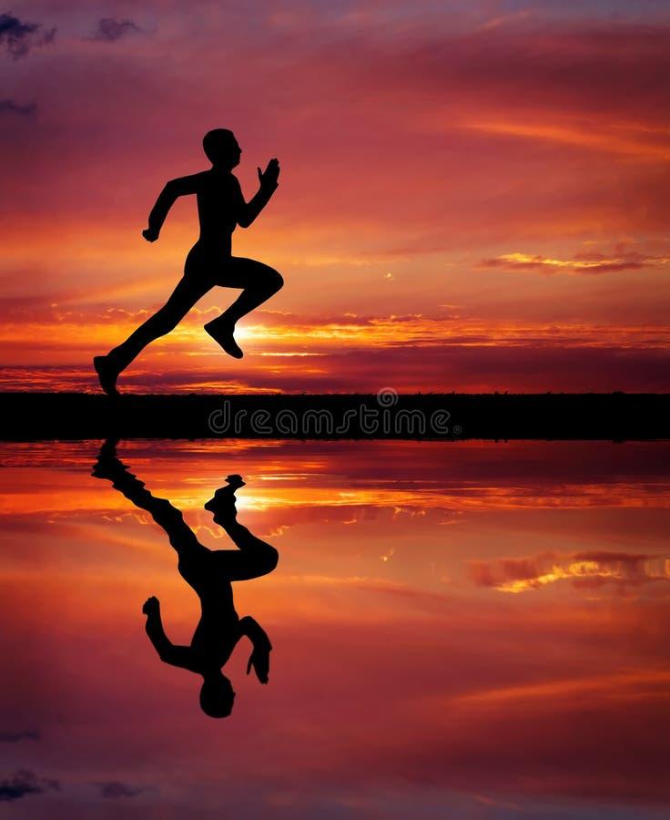 Silhueta de homem running no fundo impetuoso do por do sol. fotografia de stock