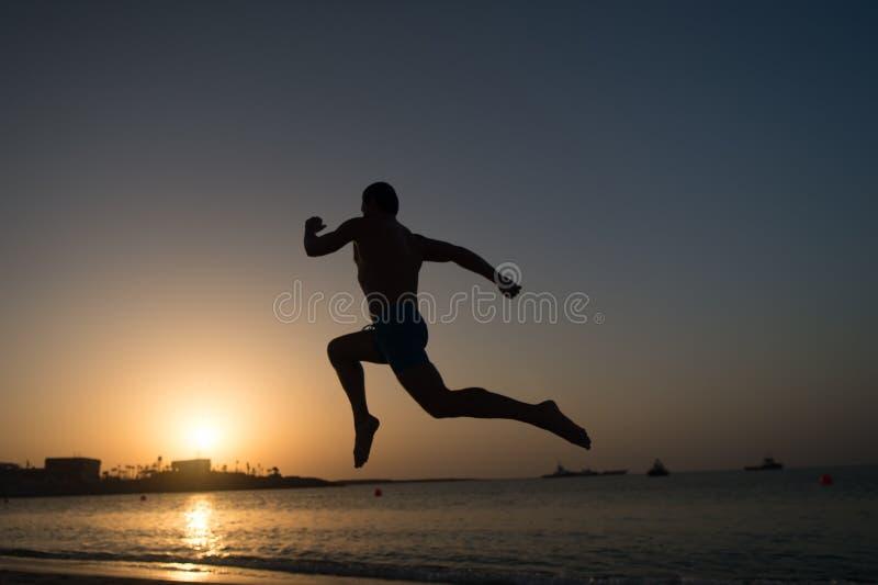 Silhueta de homem running no por do sol impetuosamente imagens de stock royalty free