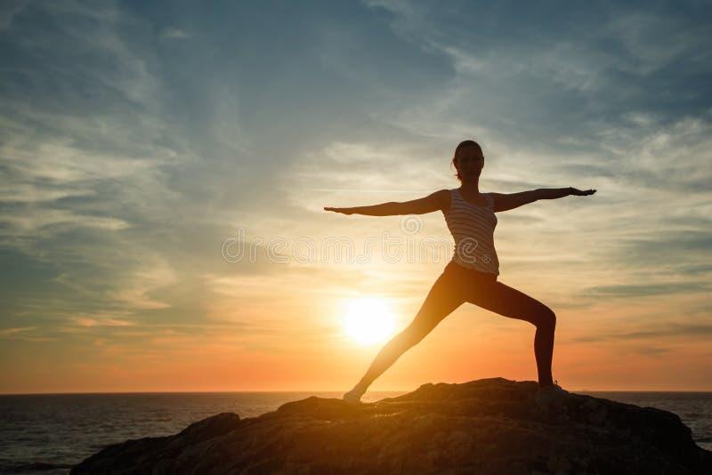 Silhueta de ioga fazendo exercícios de ginástica na praia oceânica imagens de stock royalty free