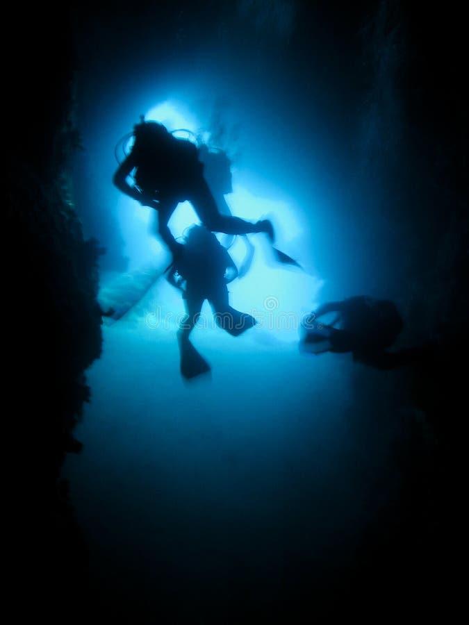 Silhueta de mergulhadores de mergulhador em uma caverna subaquática fotografia de stock royalty free
