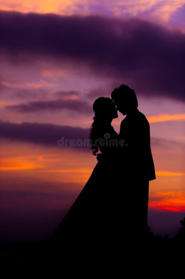 Silhueta de noivos asiáticos de abraço no por do sol fotografia de stock