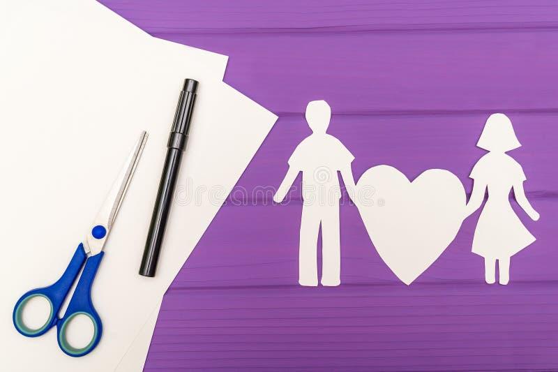 Silhueta de papel do homem e da mulher que guardam o coração fotografia de stock
