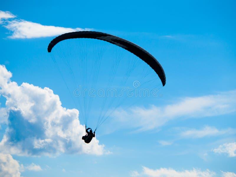 Silhueta de Paraglide com céu azul e as nuvens brancas imagem de stock royalty free
