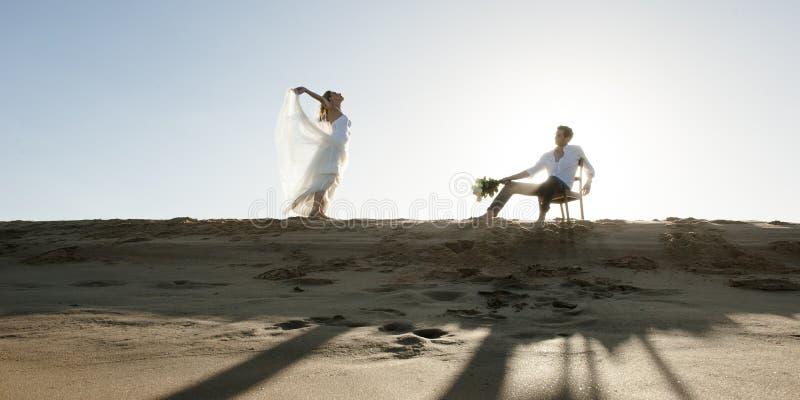 Silhueta de pares bonitos na duna de areia imagens de stock royalty free
