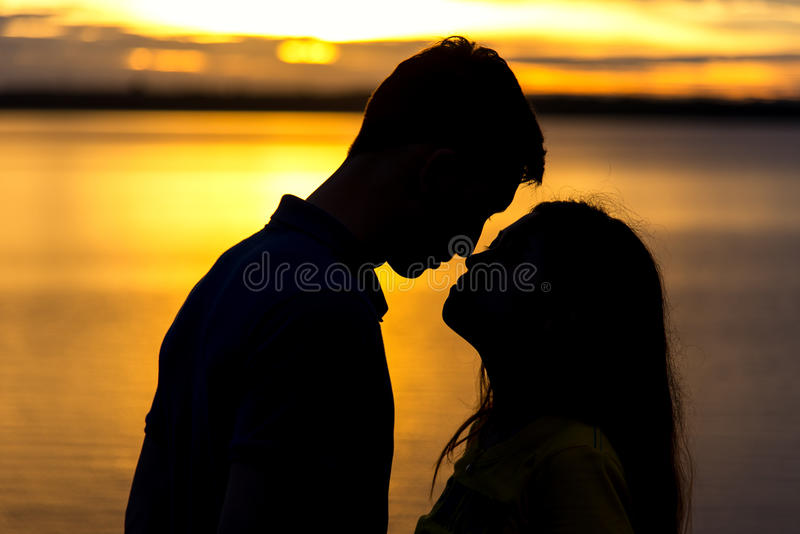 Silhueta de pares felizes no beijo do amor romântico no por do sol fotografia de stock royalty free