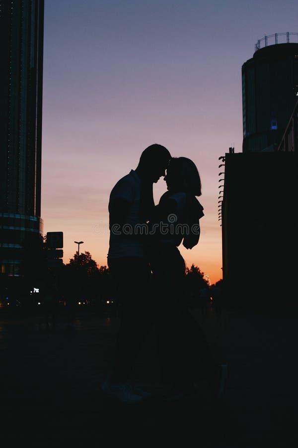Silhueta de pares felizes novos no amor que beija na rua da cidade no por do sol fotos de stock royalty free