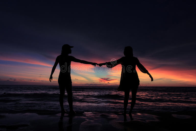 Silhueta de pares novos no amor na praia quando por do sol foto de stock