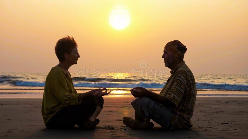 A silhueta de pares superiores senta-se e meditando junto no Sandy Beach imagens de stock royalty free