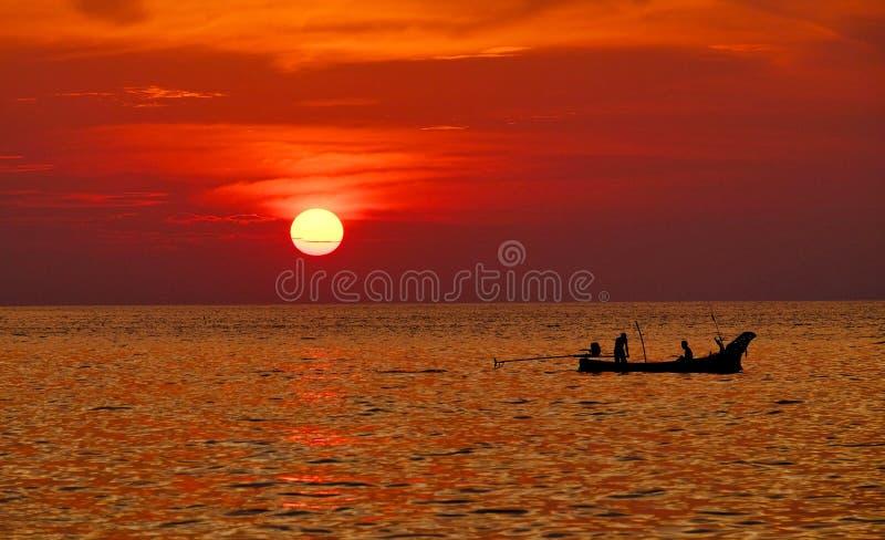 Silhueta de pessoas em um barco navegando na água com sol no céu vermelho imagem de stock