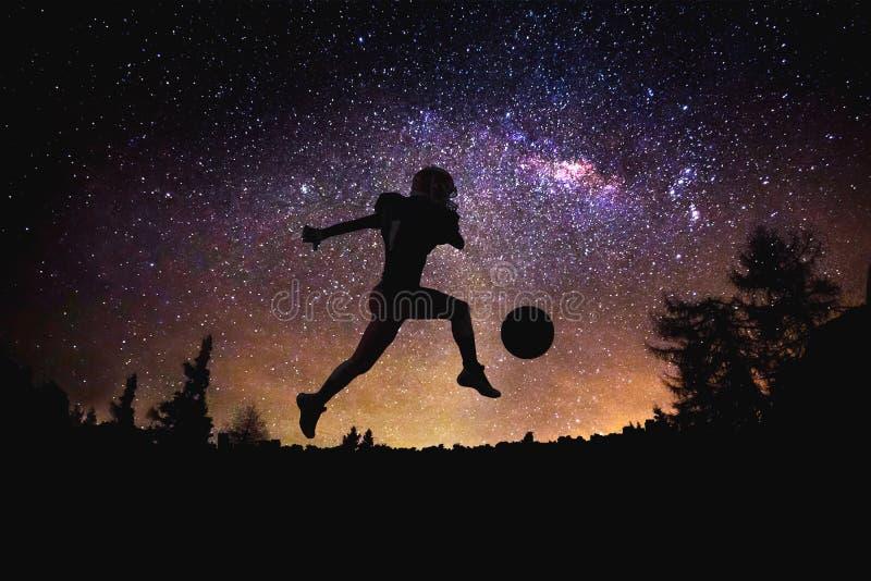 Silhueta de salto do homem do futebol americano do jogador no fundo estrelado do céu e da lua da noite foto de stock