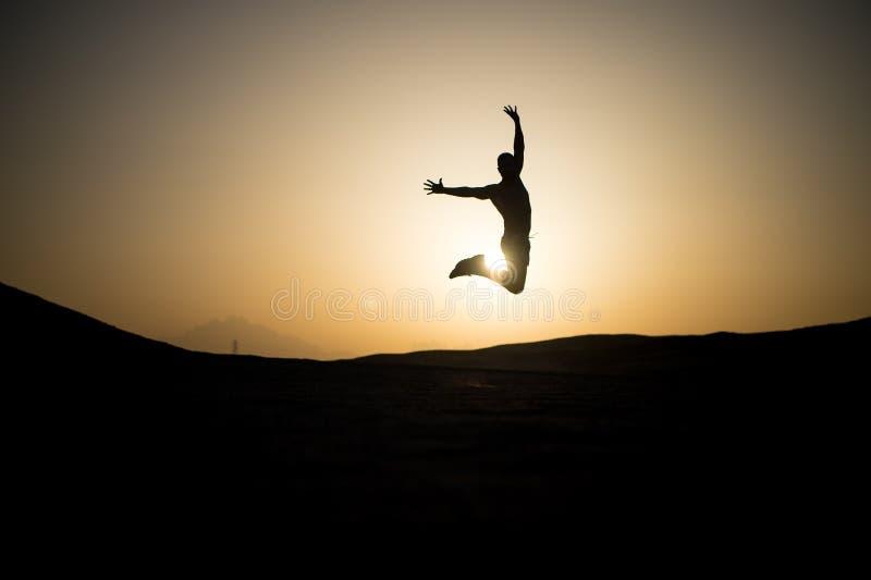 Silhueta de salto do homem no céu do por do sol imagem de stock
