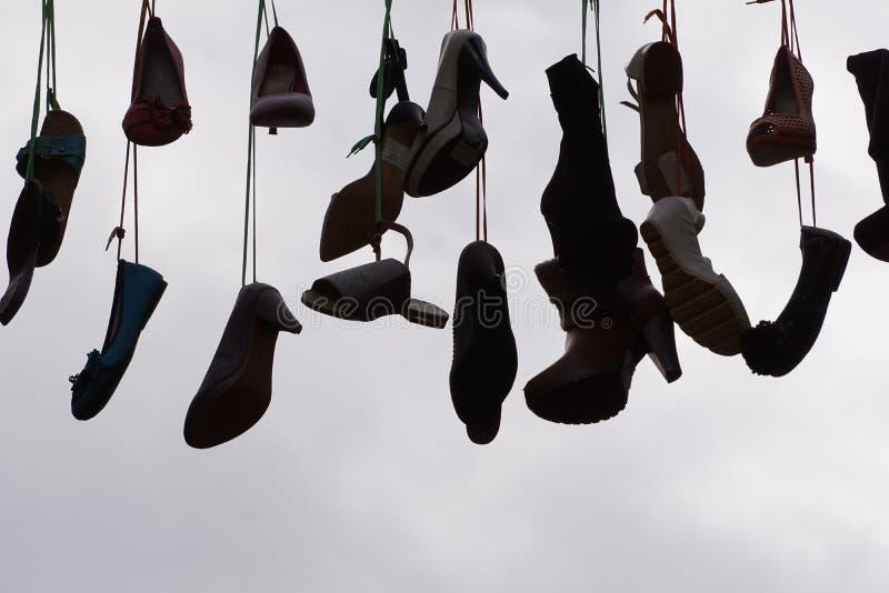 Silhueta de sapatos pendurados por cadarços contra céu nublado foto de stock
