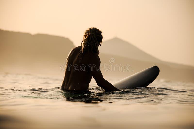 Silhueta de surfista sem camisa nas águas imagem de stock royalty free