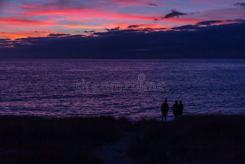 Silhueta de três pessoas no por do sol da praia em Normandy, França imagens de stock royalty free