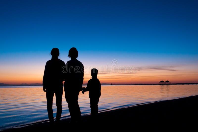 Silhueta de três povos que estão na praia no nascer do sol foto de stock