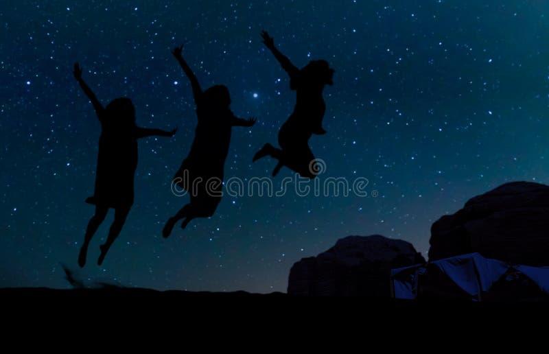 Silhueta de três povos que saltam no monte da areia, abaixo das estrelas, da Via Látea e das estrelas sobre a montanha em Wadi Ru fotografia de stock royalty free