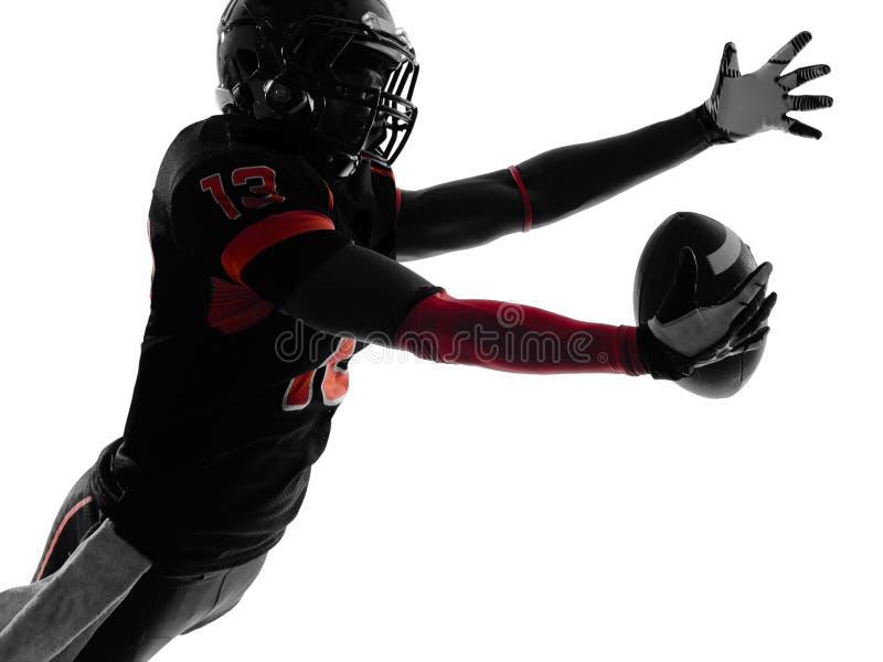 Silhueta de travamento da bola do jogador de futebol americano fotografia de stock royalty free